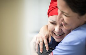 Cancer patient hugging nurse