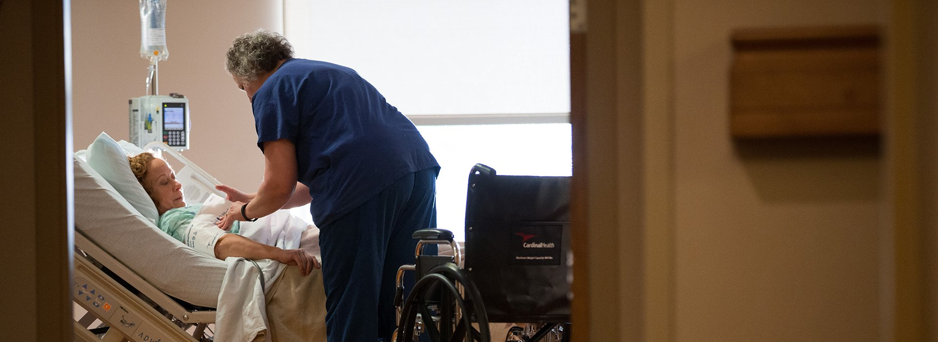 Nurse helping patient in hospital bed with wheelchair.