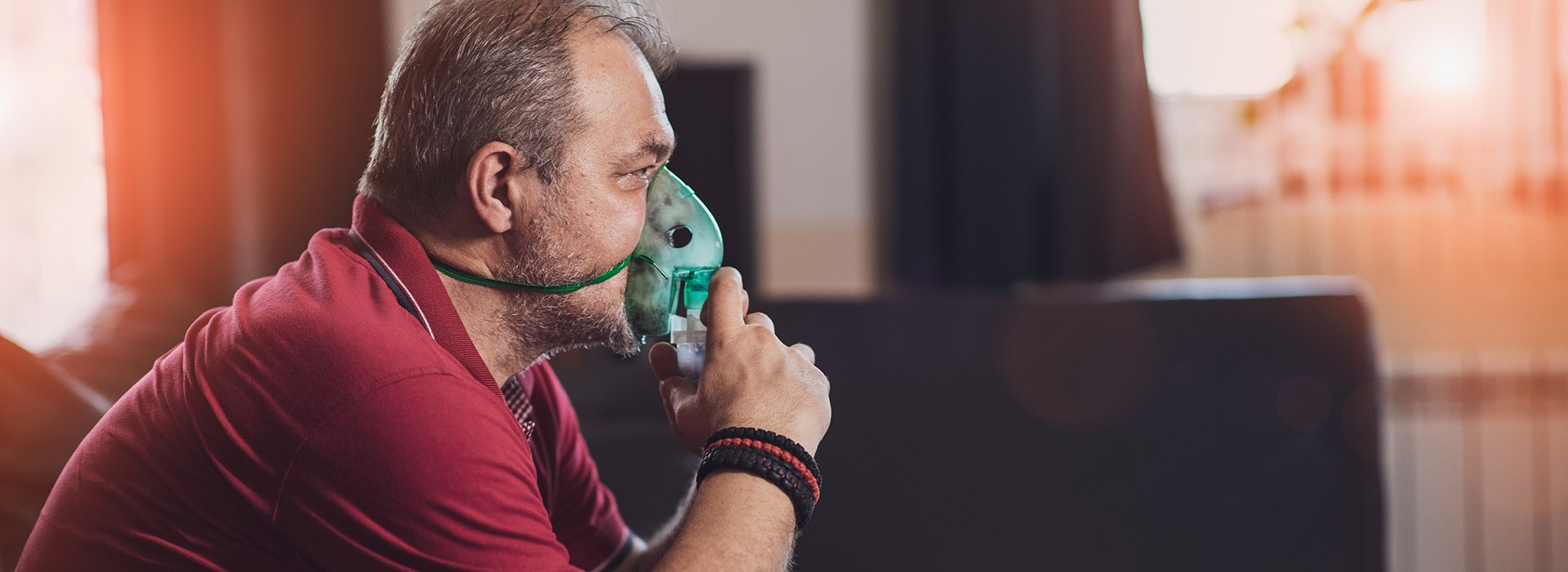 Man sitting at home wearing an oxygen mask.